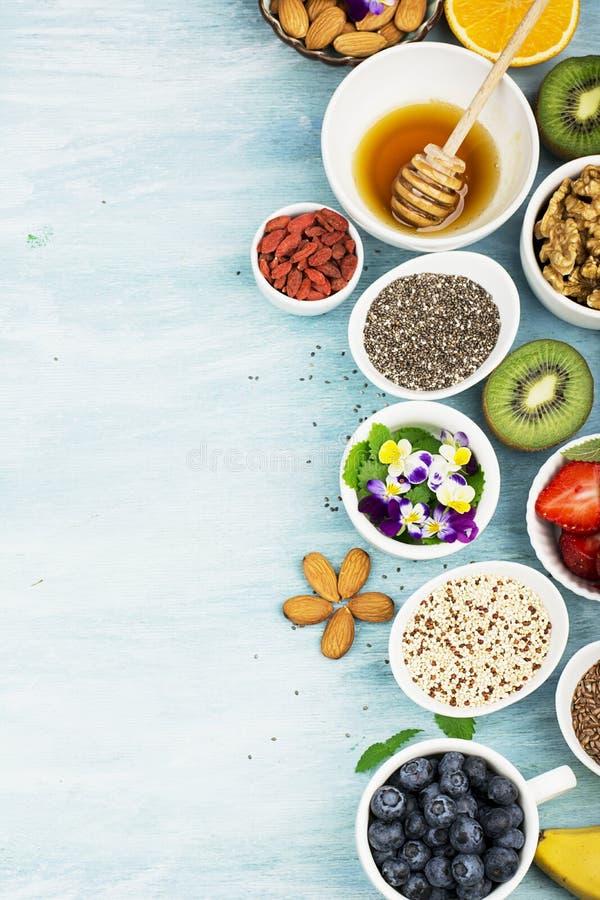 Ingredienser för sund frukost, muttrar, havremjöl, honung, bär, frukter, blåbär, apelsin, ätliga blommor, Chia frö royaltyfri bild