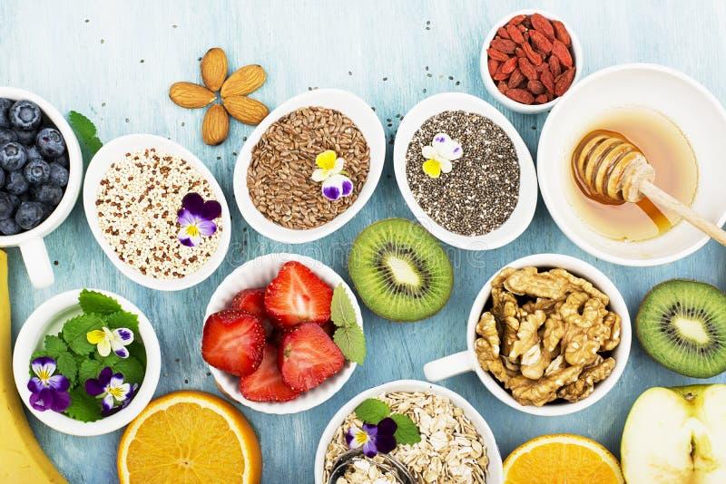 Ingredienser för sund frukost, muttrar, havremjöl, honung, bär, frukter, blåbär, apelsin, ätliga blommor, Chia frö arkivbilder