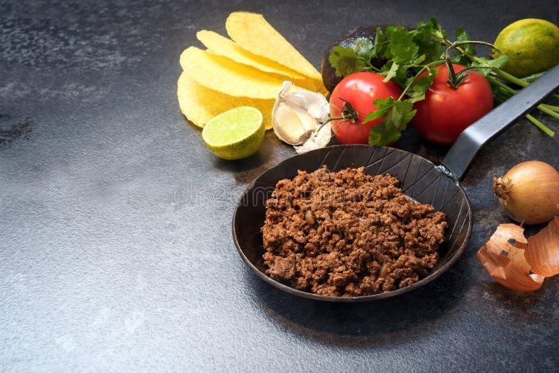 Ingredienser för taco med grillat nötkött i en panna, tomater, onio royaltyfri fotografi