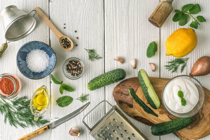 Ingredienser för tzatzikiförberedelsen på den vita träbästa sikten för tabell royaltyfri foto
