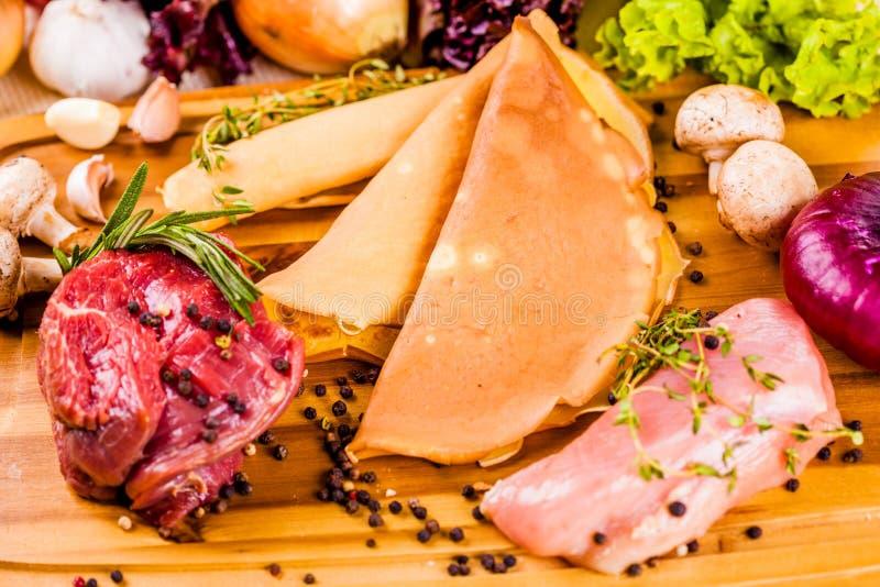 Ingredienser för välfyllda pannkakor med kött och champinjoner på träbräde royaltyfri bild