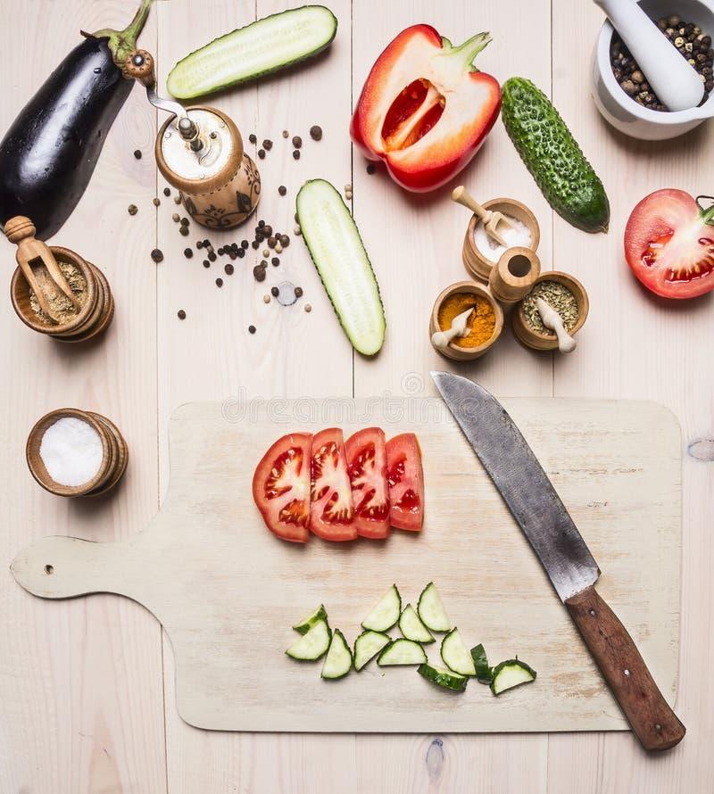 Ingredienser för vegetarisk sallad, gurkor, aubergine, röd spansk peppar, tomater, kryddor och örter, ligger bredvid skärbräda a fotografering för bildbyråer