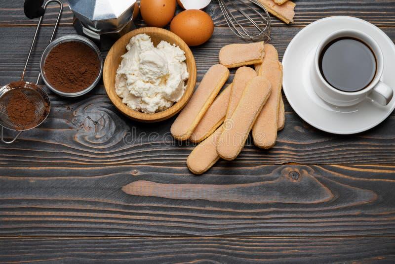 Ingredienser f?r att laga mat tiramisuen - Savoiardi ljusbruna kakor, mascarpone, kr?m, socker, kakao, kaffe och ?gg royaltyfri foto