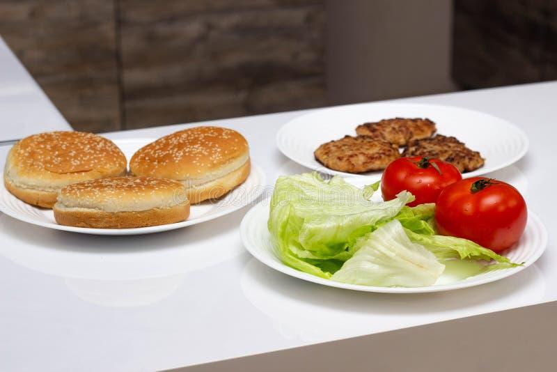 Ingredienser i köket för att laga mat den snabbmatostburgaren och hamburgaren som är hemlagat, bakgrund, hamburgarebullar arkivbilder