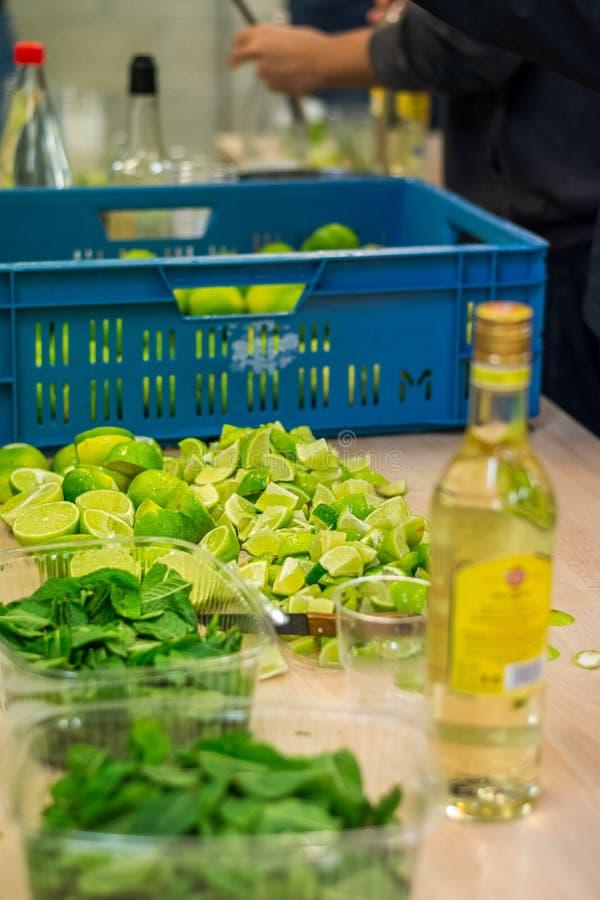 Ingredienser och förberedelse för den Mojito alkoholdrinken för ett lagparti arkivbilder