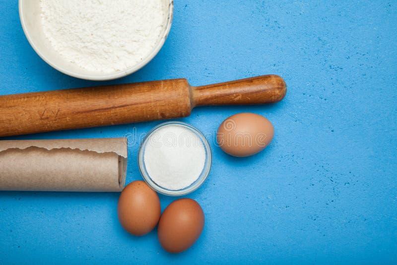 Ingredienser och matlagningredskap för framställning av en kaka eller av en efterrätt på en blå tabell royaltyfri foto