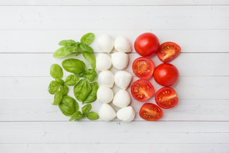 Ingredienserna f?r en Caprese sallad Basilika, mozzarellabollar och tomater på en vit bakgrund flag italienare arkivfoto