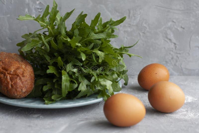 Ingrediente ajustado para o café da manhã: pão perfumado, aragula fresco e ovos foto de stock