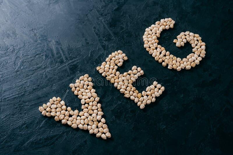 Ingrediente de alimento natural Grão-de-bico dado forma no veg da letra no fundo escuro Bio sementes da porca Grão-de-bico orgâni foto de stock royalty free
