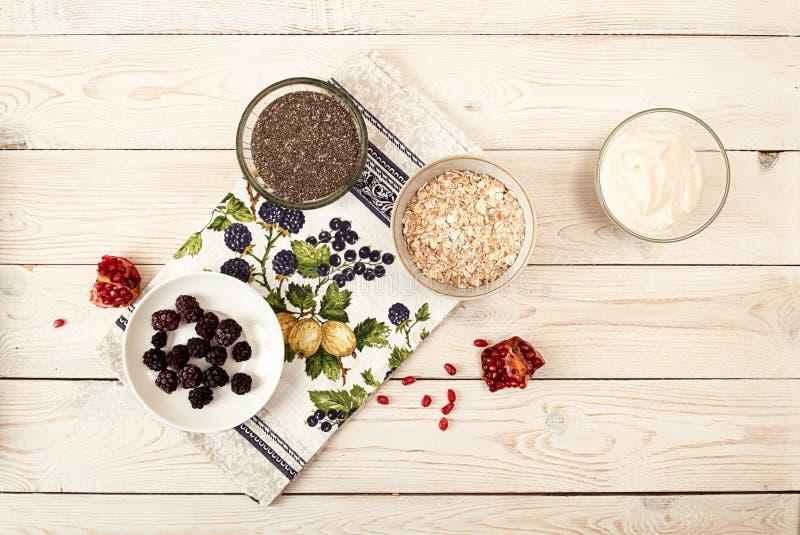 Ingrediente para preparar el desayuno sano: chia, muesli, congelado fotografía de archivo