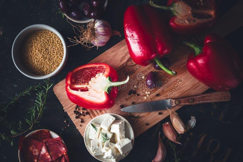 Ingrediente per la cottura con il peperone, il miglio, il feta, il prosciutto di Coppa, l'aglio e l'erba aromatica fotografia stock
