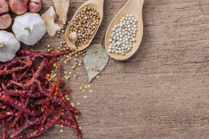 Ingredientes alimentarios, grano de pimienta y pimientas de chiles secas rojas en woode imágenes de archivo libres de regalías