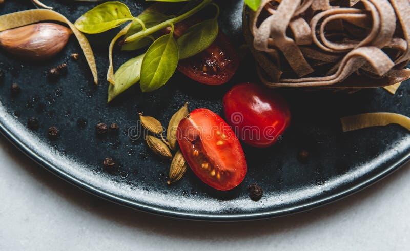 Ingredientes alimentarios italianos en una placa de cerámica imagenes de archivo