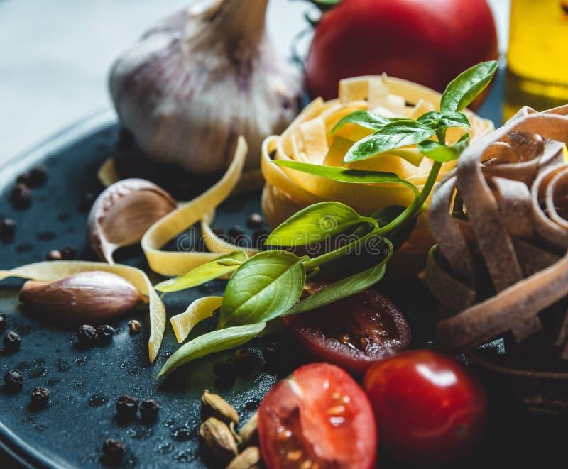 Ingredientes alimentarios italianos en una placa de cerámica foto de archivo
