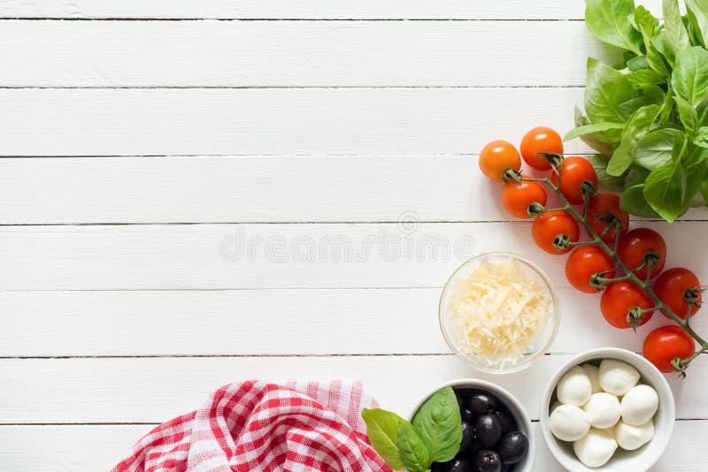 Ingredientes alimentarios italianos para cocinar en la tabla blanca con el espacio de la copia para el texto imagen de archivo libre de regalías