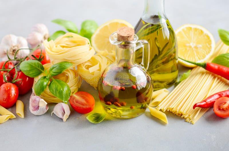 Ingredientes alimentarios italianos – pastas, tomates, albahaca y aceite de oliva en fondo concreto gris foto de archivo libre de regalías