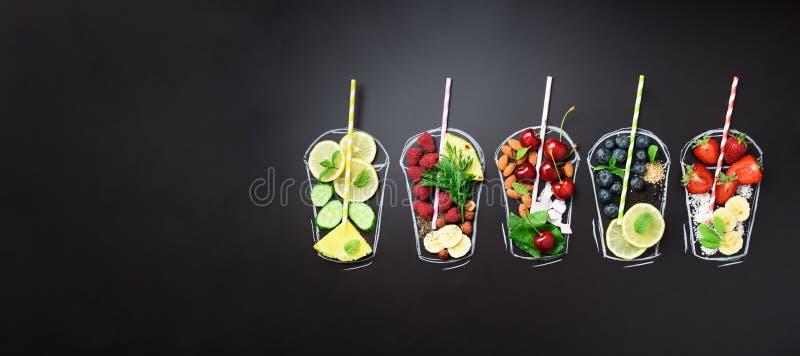 Ingredientes alimentarios para el smoothie o el jugo de mezcla sobre el vidrio pintado sobre la pizarra negra Visión superior con fotos de archivo libres de regalías