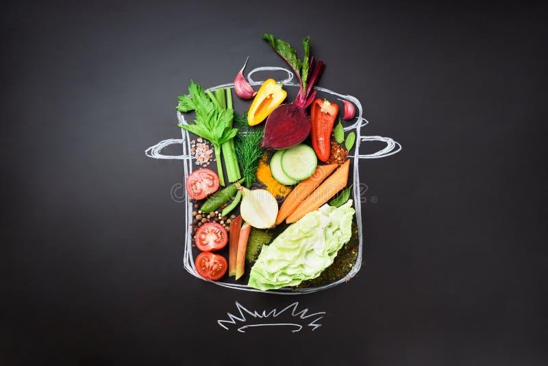 Ingredientes alimentarios para mezclar la sopa cremosa en pintado stewpan sobre la pizarra negra Visión superior con el espacio d fotografía de archivo libre de regalías