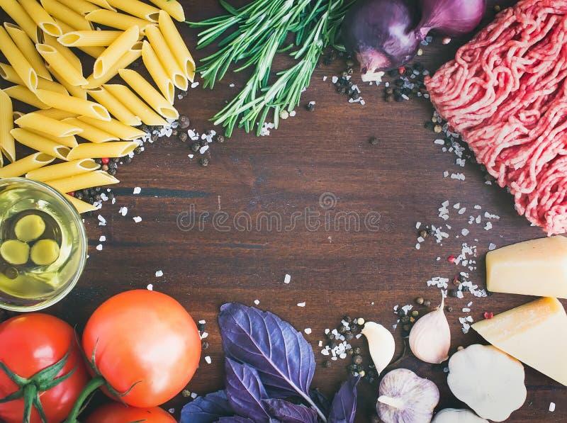 Ingredientes boloñeses de las pastas: penne, carne picadita, tomates, albahaca imagen de archivo libre de regalías