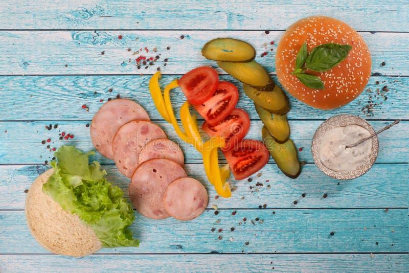 Ingredientes con el jamón de la salchicha, elementos, encimera desmontada, de madera de la hamburguesa fotografía de archivo libre de regalías