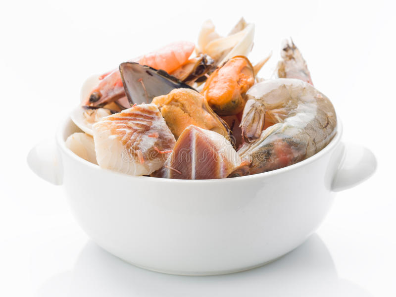 Ingredientes crudos para preparar la sopa de los mariscos en cuenco de la loza de barro fotografía de archivo
