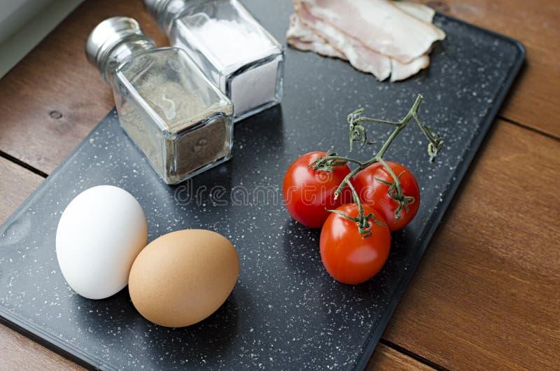 ingredientes crus para ovos mexidos, a f?rmula fresca, os tomates sal do bacon dos ovos e a pimenta na placa de corte imagem de stock
