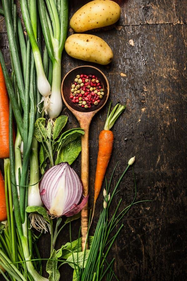 Ingredientes da colher de madeira e dos legumes frescos para cozinhar no fundo escuro foto de stock
