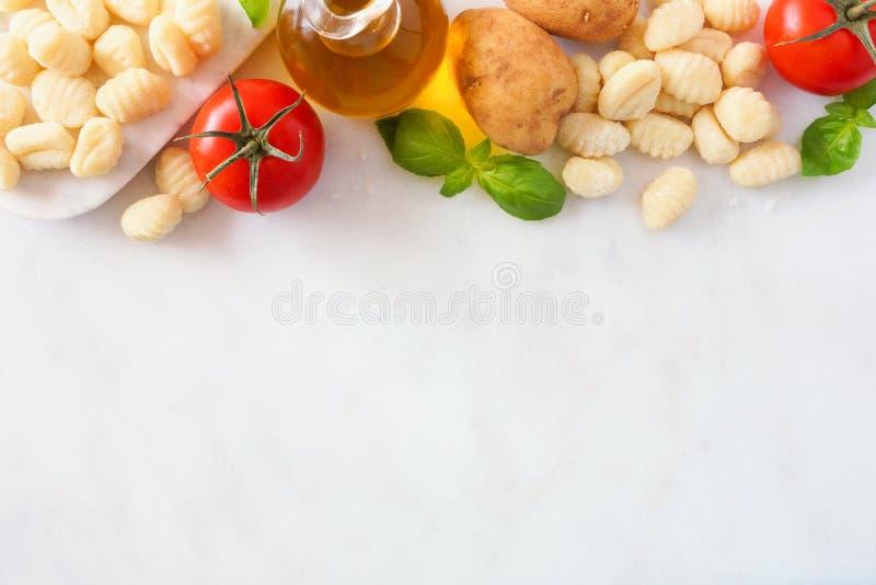 Ingredientes da refeição do Gnocchi, tomates, azeite, batatas e manjericão, acima da vista, beira superior no mármore branco fotos de stock royalty free
