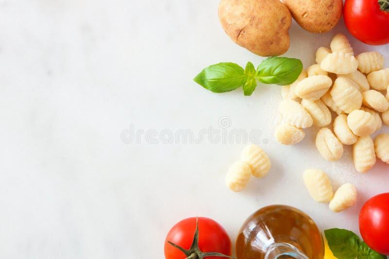 Ingredientes da refeição do Gnocchi, tomates, azeite, batatas e manjericão, vista superior, beira lateral no mármore branco imagem de stock royalty free