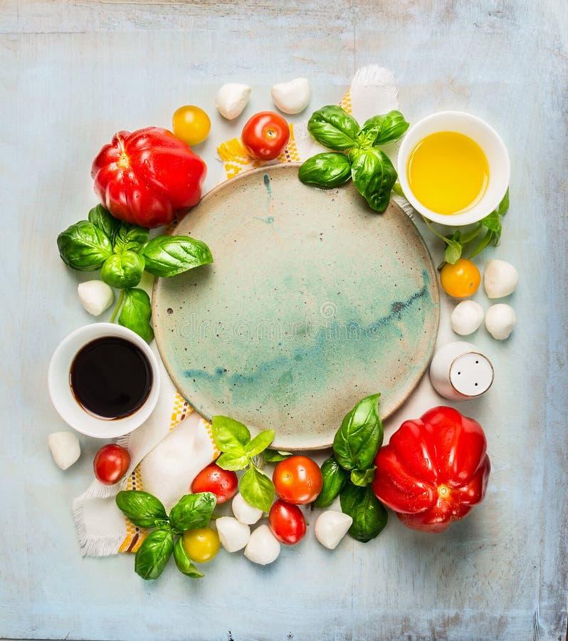 Ingredientes da salada dos tomates da mussarela com manjericão, óleo e vinagre balsâmico em torno da placa vazia no fundo de made fotografia de stock royalty free