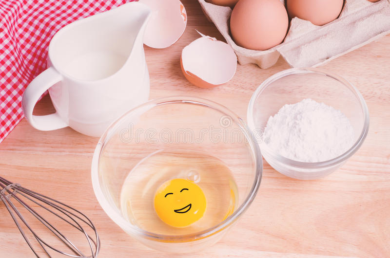 Ingredientes das cookies Egg com a cara smilling na bacia, farinha, leite foto de stock