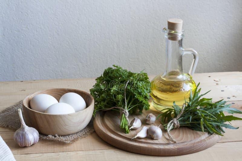 Ingredientes de alimento Óleo, ovos, alho e ervas na tabela de madeira fotografia de stock royalty free