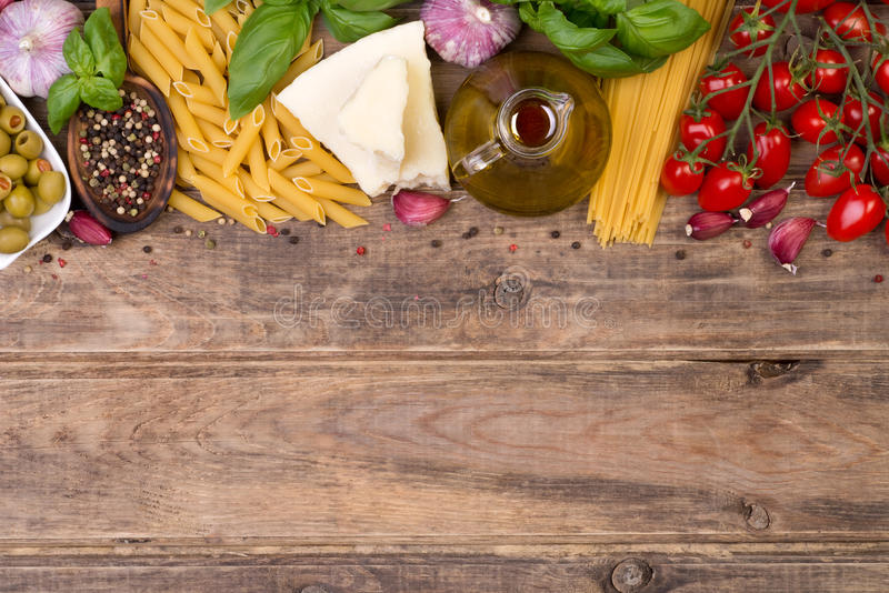 Ingredientes de alimento italianos no fundo de madeira