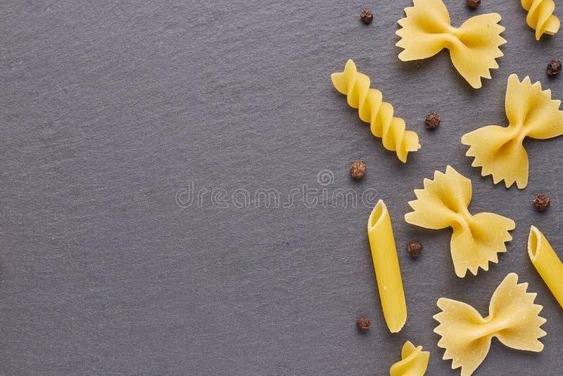 Ingredientes de alimento para cozinhar a massa no fundo da ardósia preta com abundância do espaço livre para seu projeto fotografia de stock royalty free