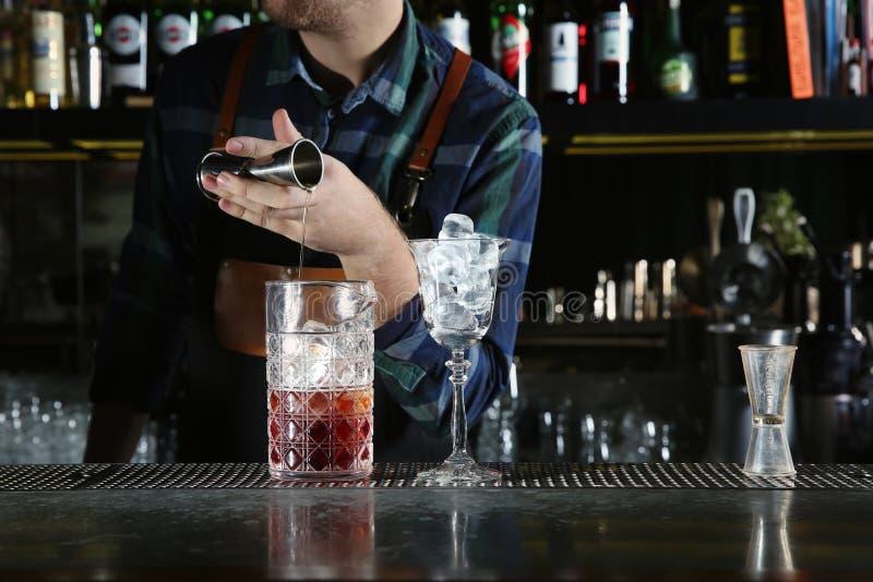 Ingredientes de colada del cóctel del camarero en el vidrio de mezcla en el contador en pub foto de archivo libre de regalías