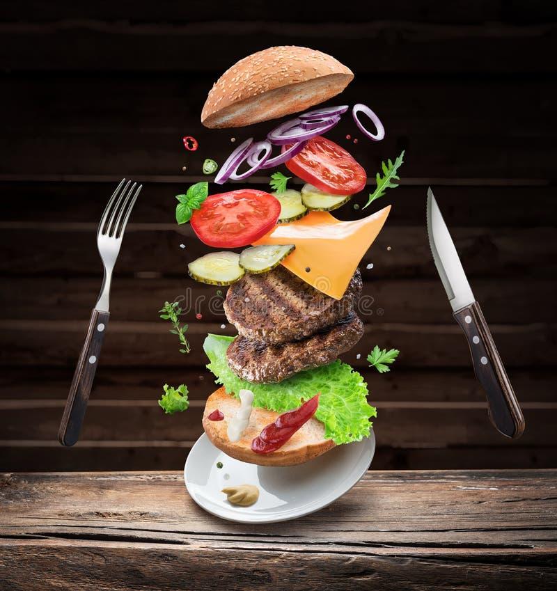 Ingredientes de la hamburguesa que caen abajo uno por uno para crear una comida perfecta Imagen conceptual colorida de cocinar de fotografía de archivo libre de regalías