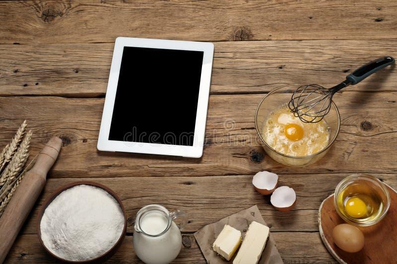 Ingredientes de la hornada con la tableta blanca imágenes de archivo libres de regalías
