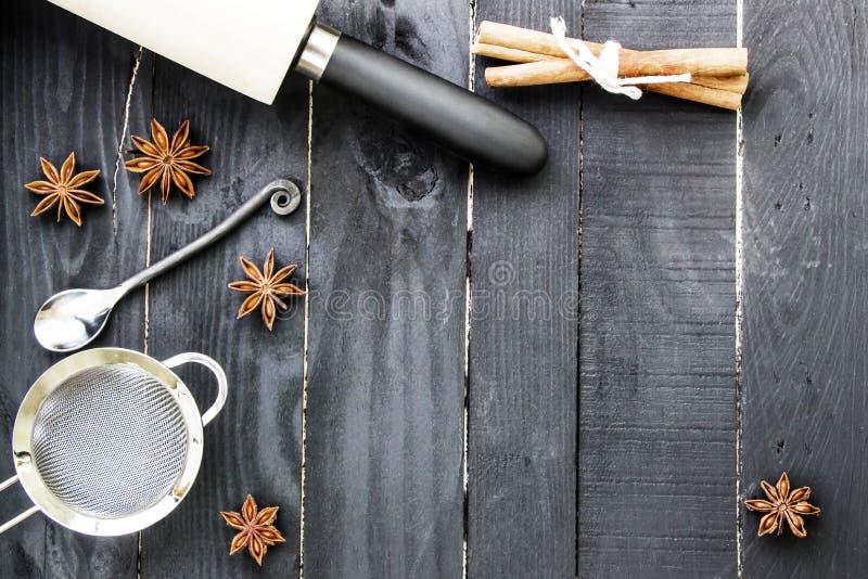 Ingredientes de la hornada en el fondo de madera rústico negro Herramientas, nueces y especias de la cocina en la tabla de madera imagenes de archivo