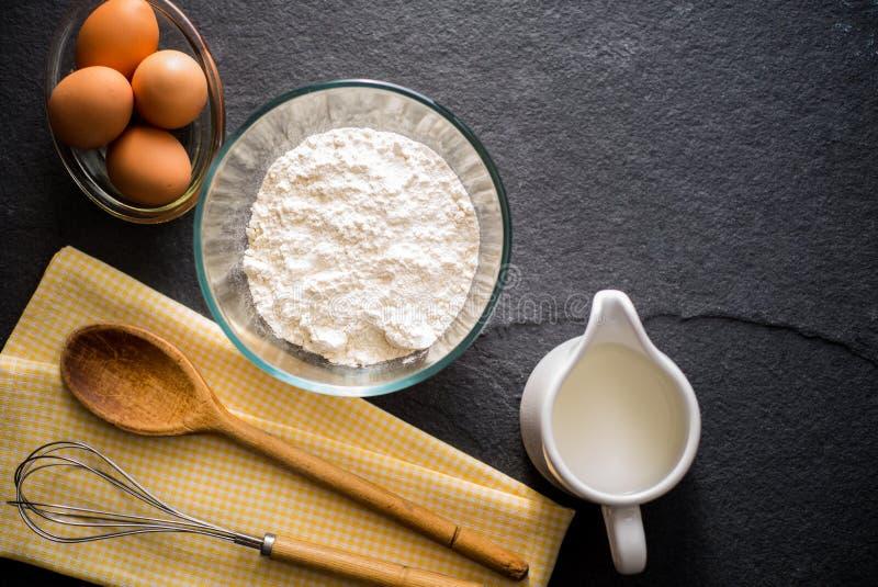 Ingredientes de la hornada - harina, leche, huevos con un batir imágenes de archivo libres de regalías