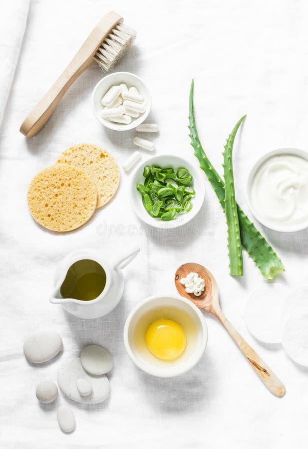 Ingredientes de la mascarilla del áloe - áloe, yogur, huevo, aceite de oliva y accesorios de la belleza en el fondo ligero, visió fotos de archivo