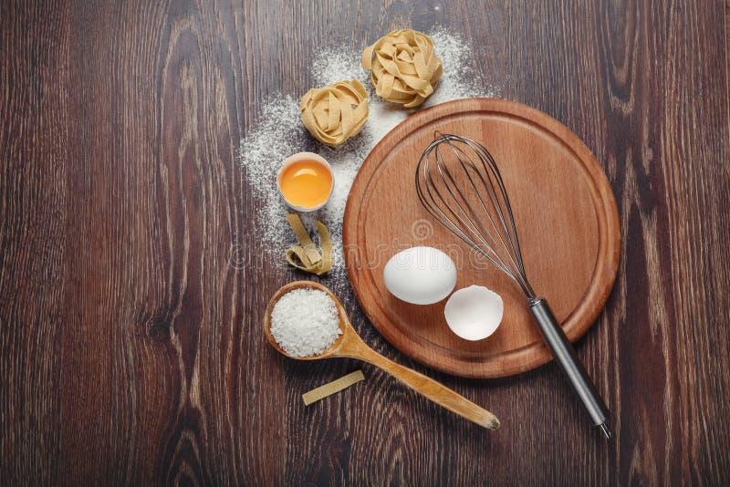 Ingredientes de la panadería Flour con los huevos crudos para las pastas de la pasta en un fondo de madera fotos de archivo