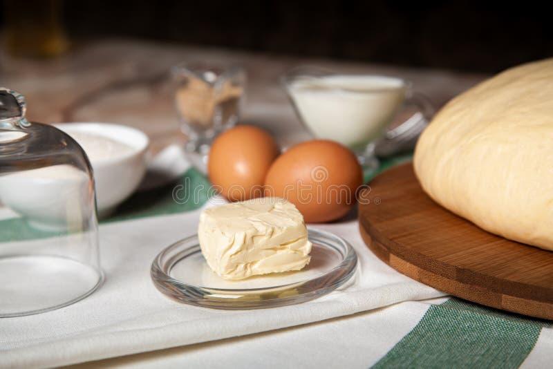 Ingredientes de la panader?a En la tabla es la mantequilla, huevos, leche, levadura, azúcar imágenes de archivo libres de regalías