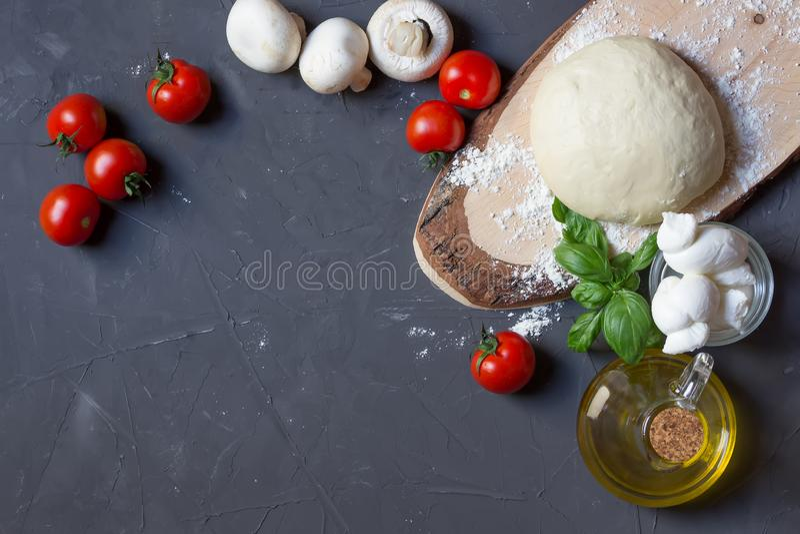Ingredientes de la pizza en el fondo gris con el espacio de la copia, pasta, tomates, setas, albahaca, mozzarella, aceite de oliv imagen de archivo