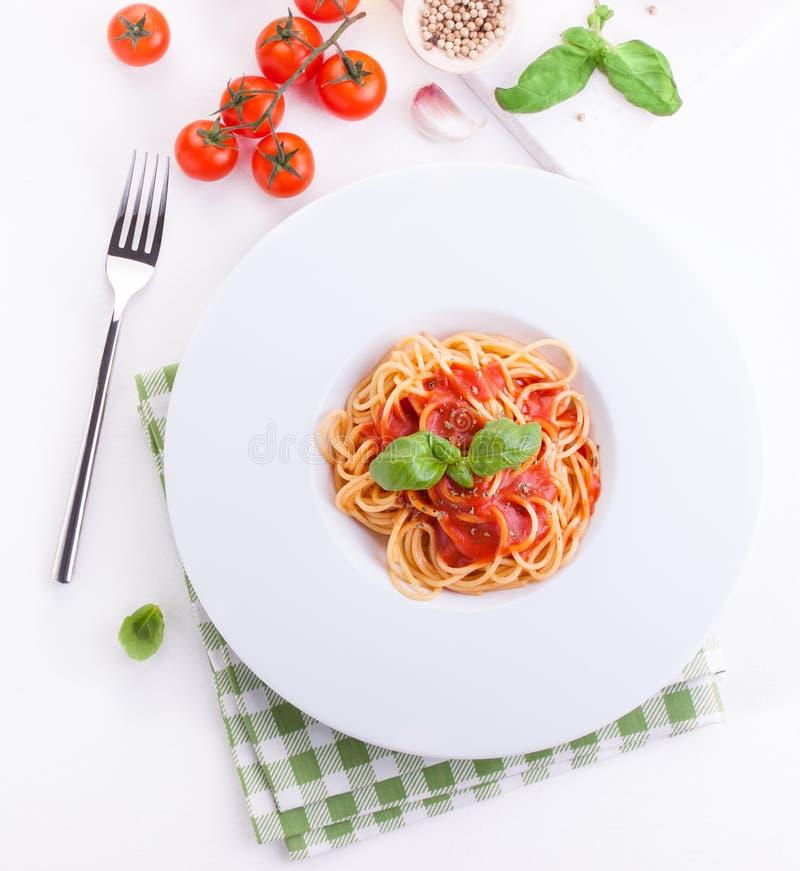 Ingredientes de las pastas - tomates, aceite de oliva, ajo, hierbas italianas, albahaca fresca, sal y espaguetis en un fondo de p fotos de archivo