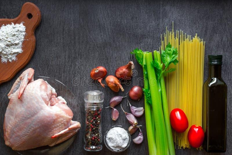 Ingredientes de las pastas Tomates de las pechugas de pollo, de cereza, pastas de los espaguetis, elery, especias y ajo en la tab foto de archivo