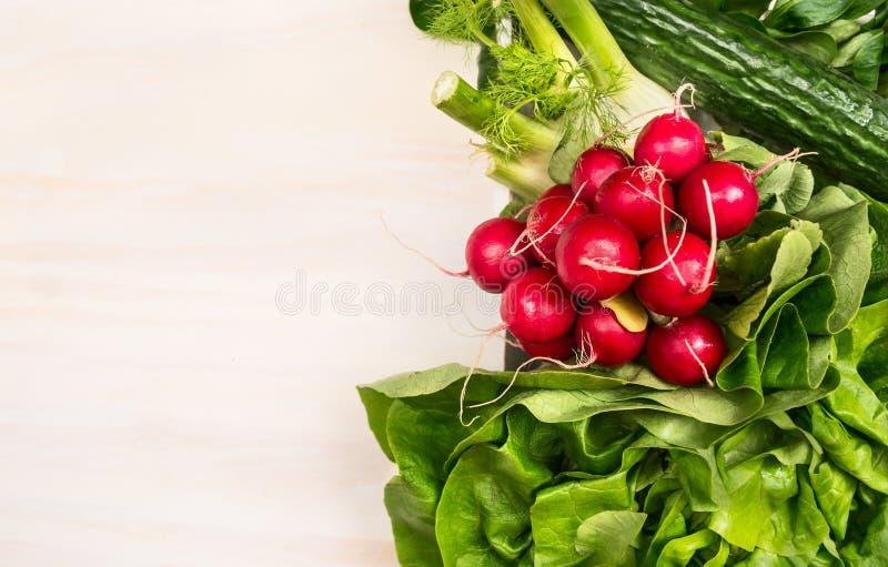 Ingredientes de las verduras para la ensalada: rábano, pepino, lechuga en el fondo de madera blanco, visión superior imagen de archivo
