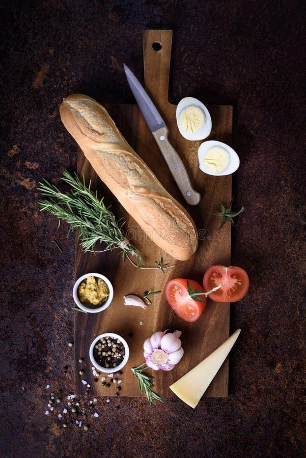Ingredientes del bocadillo del Baguette - queso, huevo, tomates, mostaza en el tablero de madera Visión superior, espacio de la c imagen de archivo
