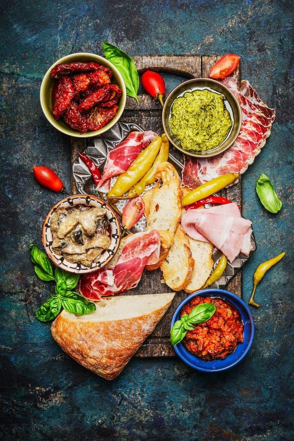 Ingredientes deliciosos de los antipasti para el bruschetta o el crostini que hace en el fondo rústico, visión superior imagen de archivo