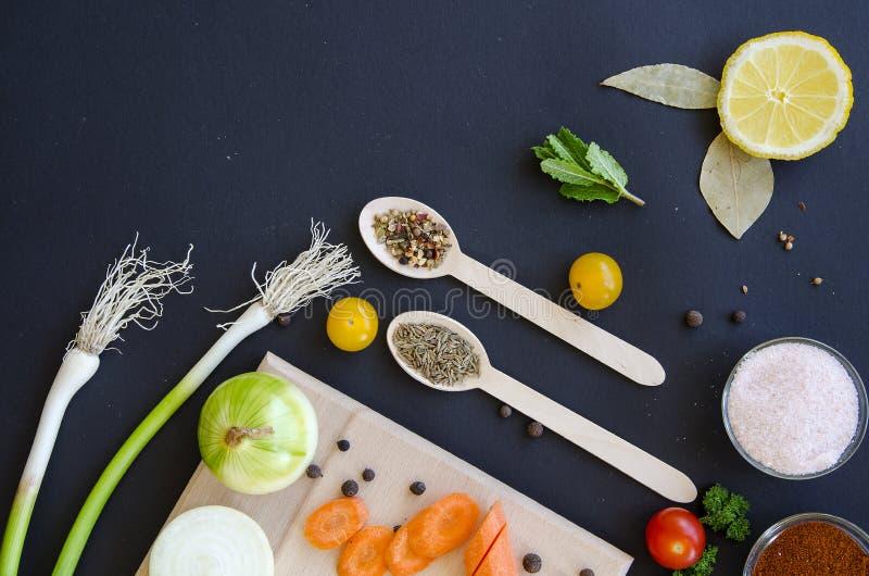 Ingredientes deliciosos frescos para o cozimento saudável ou salada que faz no fundo do preto escuro e na placa de corte de madei foto de stock royalty free