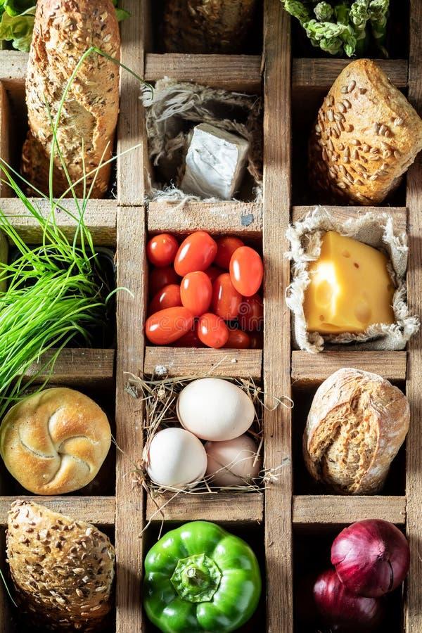 Ingredientes deliciosos para o sanduíche em uma caixa de madeira velha imagem de stock